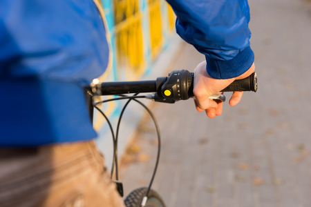 hand brake: Young man out riding his bicycle with a close up view from behind of his hand on the brake lever and handlebar