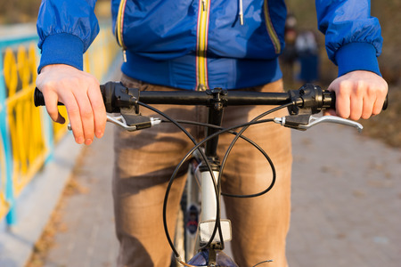 handlebars: Close up detail of a man riding a bicycle along a pathway approaching the camera with focus to his hands on the handlebars Stock Photo