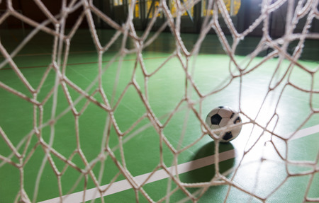 goalpost: Atmospheric image of a backlit soccer ball in a goalpost in a darkened indoor court viewed through the net on the goal Stock Photo
