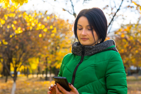 anorak: Young woman in a colorful green anorak standing outdoors in an autumn park with vivid yellow foliage reading an sms on her mobile