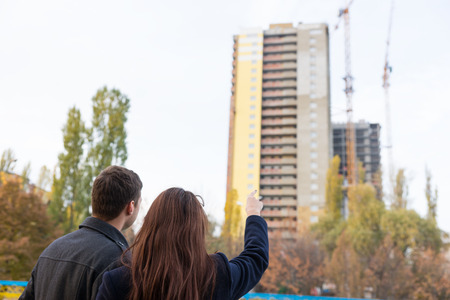 looking at: Head and Shoulders Rear View of Young Unrecognizable Couple Pointing Up at High Rise Residential Apartment Building Under Construction - Couple Looking at Their New Condo Apartment Being Built