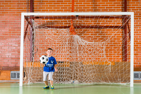 indoor soccer: Young boy playing goal keeper for an indoor soccer game holding the ball in his hand as he watches the players