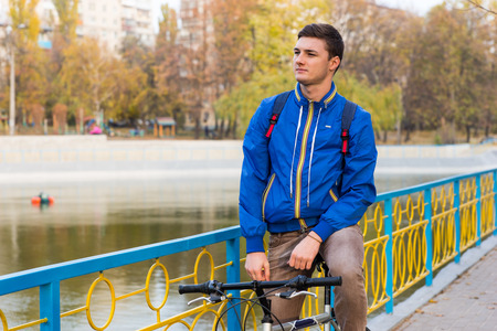 three quarter length: Three Quarter Length of Young Man on Bicycle Taking a Break on Waterfront Promenade in Park in Autumn, Looking into the Distance Thoughtfully