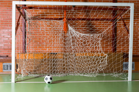all weather: Soccer ball in an empty goal post on an all weather indoor court in a brick building, close up view Stock Photo