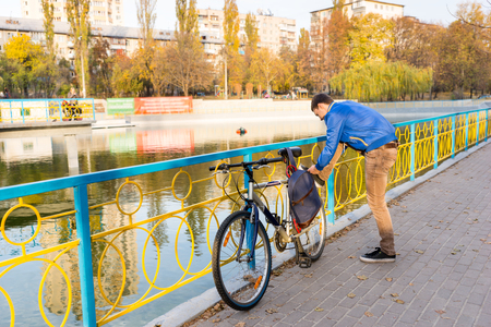 alongside: Young man stopping to tie his shoelaces as he cycles along a footpath alongside a bright metal railing and canal or lake in a park