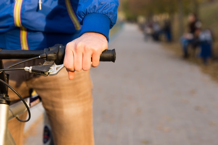 anorak: Man riding his bicycle outdoors in a park with a close up view from the front of his hand on the handlebar and copy space alongside Stock Photo