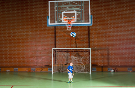 indoor soccer: Young boy playing indoor soccer standing in the goalposts watching as a ball loops through the air towards the goal Stock Photo