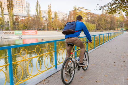Full Length Rear View of Young Man Wearing Backpack and Riding Bicycle on Waterfront Promenade Through Urban Park in Autumn