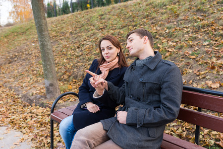 tryst: Young Fashionable Couple Wearing Coats Sitting Together on Park Bench on Chilly Autumn Day - Woman is Looking at Camera While Man is Pointing into the Distance Stock Photo