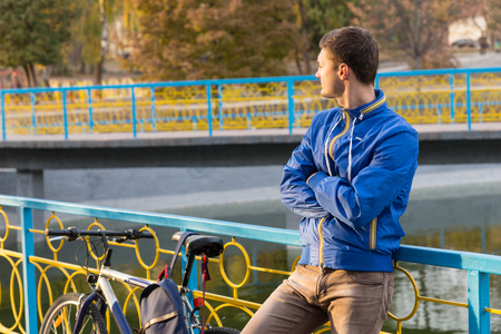 expectant arms: Three Quarter Length Portrait of Young Man Standing with Arms Crossed and Looking into the Distance While Leaning Against Colorful Railing Next to Bicycle on Bridge in Urban Park on Autumn Day Stock Photo