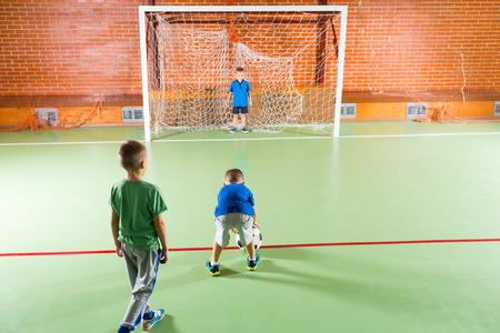 lining up: Three small boys practicing their soccer on an indoor court lining up to try for goal