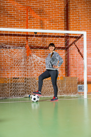 all weather: Smiling athletic young soccer Mum standing in the goalposts of an indoor court with her foot on the ball Stock Photo