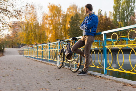rendezvous: Man standing waiting at a rendezvous leaning against colorful metal railings with folded arms and his bicycle alongside him
