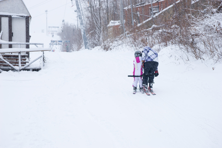 bending down: Child learning to ski with an adult bending down giving guidance in a snowy winter landscape at a ski resort, view from the rear