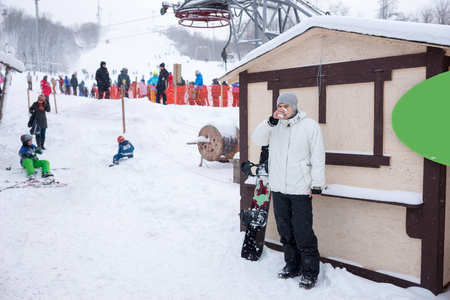 ski lodge: Young snowboarder warming up with coffee as he stands near a ski run at a resort with tourists visible as a blur in the background