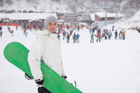 ski lodge: Young man with his bright green snowboard at a ski resort standing clasping it under his arm against a snowy background with distant people and a lodge