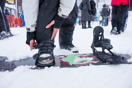 bending down: Person putting on his snowboard bending down in the winter snow at a resort tightening the straps, close up view Stock Photo