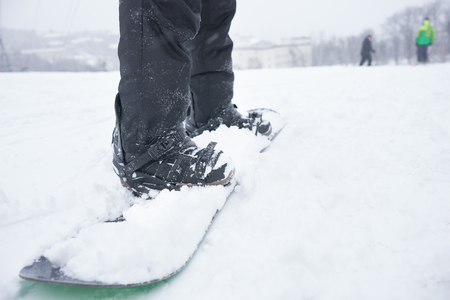 low  angle: Legs and board of a snowboarder on a snowy winter mountain, low angle with skiers visible in the distance