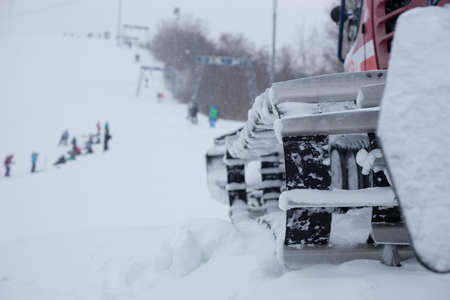 snow plow: Close up of a snow plow on a ski resort parked alongside a run with skiers and snowboarders Stock Photo