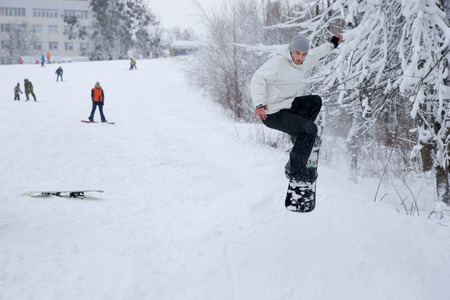 descends: Young man jumping into the air on his snowboard as he descends a run at a winter ski resort, with copy space