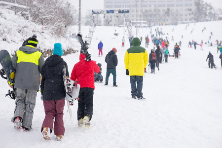 ski walking: Tourists trudging through snow at a ski resort walking away from the camera towards distant hotels and accommodation Stock Photo