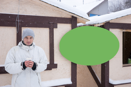 ski lodge: Calm young man in coat with hot drink standing next to blank green sign with copy space at a ski hut Stock Photo