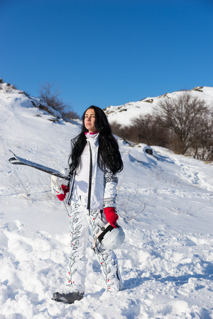 ski walking: Serious long haired female skier with white snowsuit, red gloves and ski equipment walking up hillside under sunny blue sky Stock Photo