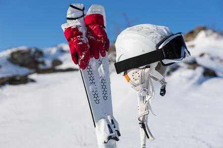 Sneeuw afgestoft paar luchten met rode handschoenen vastgebonden op hen naast de helm en bril op palen met winter berg achtergrond Stockfoto