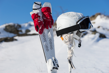 Snow dusted pair of skies with red gloves tied on them next to helmet and goggles on poles with winter mountain background
