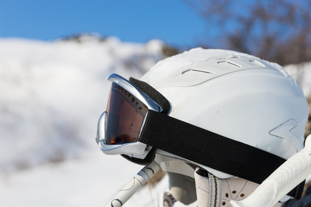 strapped: Close up of white ski helmet with goggles strapped on top in between poles with snowy mountain background