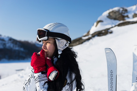 mountainside: Head and Shoulders Close Up of Young Woman with Long Dark Hair Wearing Helmet and Goggles Standing on Snowy Mountainside Looking into the Distance and Warming Hands with Breath on Sunny Day