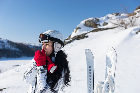 mountainside: Waist Up of Young Woman with Long Dark Hair Wearing Ski Goggles and Helmet Standing Next to Skis and Warming Hands with Breath While Looking into the Distance on Sunny Snowy Mountainside
