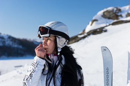 snow break: Close Up Head and Shoulders of Woman Wearing Helmet and Taking a Break from Skiing to Blow Hot Breath on Hands to Warm Them Up on Snow Covered Mountainside