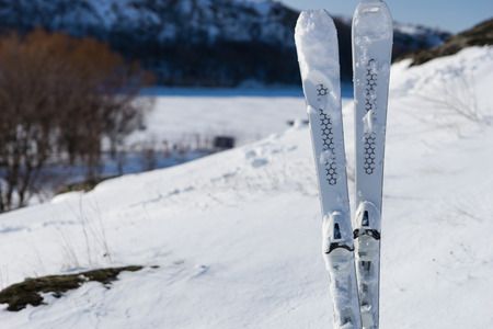 snow break: Still Life of Downhill Skis Standing Upright on Snow Covered Mountainside with View of Valley in Background on Sunny Day with Bright Sunshine
