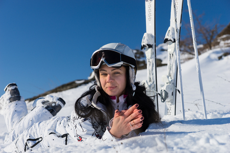 Close Up of Young Woman Wearing White Ski Suit and Lying on Stomach on Snow Covered Mountainside Next to Skis and Poles on Bright Day with Blue Sky and Warm Sunshine photo