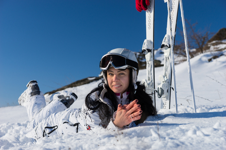 Full Length Portrait of Smiling Young Woman Wearing Helmet and Goggles Lying on Stomach on Snow Covered Mountainside with Skis and Poles Nearby on Day with Blue Sky and Warm Sunshine photo
