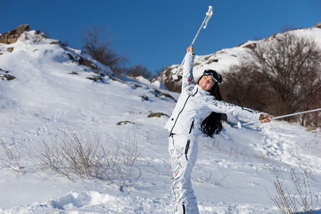 Full Length Portrait of Smiling Young Woman with Long Dark Hair Taking a Break from Skiing and Holding Poles Above Head, Happy Female Skier Celebrating Beautiful Day and Freedom photo