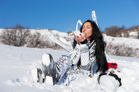 Full Length of Playful Young Woman with Long Dark Hair Sitting on Snow Covered Mountainside, Enjoying Warm Sunshine and Blowing Handful of Fluffy Snow with Skis Nearby on Bright Day with Blue Sky photo