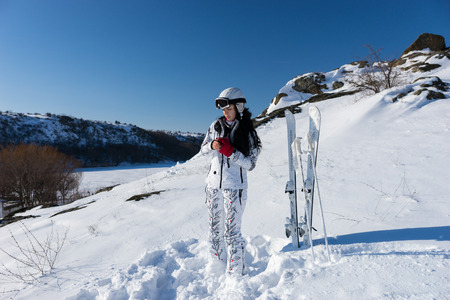 Full Length Candid of Young Woman Wearing White Ski Suit and Helmet Putting on Red Gloves and Standing Next to Skis and Poles on Snow Covered Mountainside on Bright Day with Warm Sunshine and Blue Sky photo