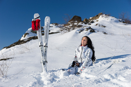 Full Length of Smiling Young Woman with Long Dark Hair Sitting on Snow Covered Mountainside with Skis and Poles Nearby and Enjoying Warm Sunshine photo