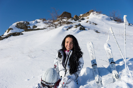 Waist Up Portrait of Smiling Young Woman with Long Dark Hair Holding Helmet and Sitting on Snow Covered Mountainside with Skis and Poles Nearby on Bright Day with Warm Sunshine and Blue Sky photo