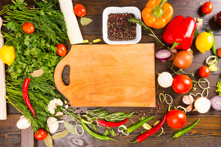 High Angle View of Empty Wooden Cutting Board on Rustic Table Scattered with Fresh Herbs and Spices and Colorful Vegetables and Copy Space Stock Photo