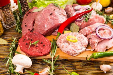 Top-down-Ansicht auf überfüllten Sortiment von verschiedenen Fleischsorten, Paprika, Tomaten, Kräutern, Gewürzen und anderen Zutaten