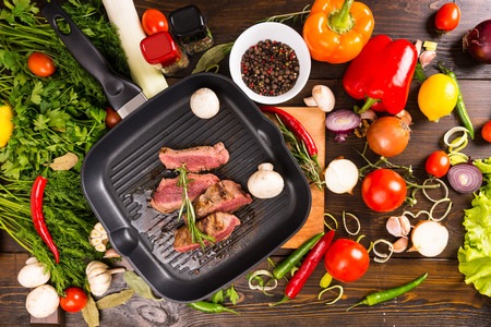 griddle: High Angle View of Sliced Rare Roast Beef Sizzling on Hot Cast Iron Frying Pan Surrounded by Fresh Ingredients - Colorful Vegetables, Fresh Herbs and Seasonings Stock Photo