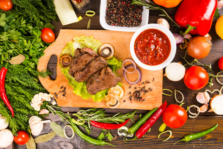 bounty: High Angle View of Small Pieces of Beef Resting on Wooden Cutting Board with Salsa Dip and Surrounded by Bounty of Fresh Colorful Vegetables, Herbs and Spices