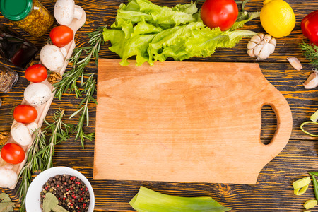 potherbs: Delicious tomatoes, mushrooms, green leaf lettuce, lemon, garlic and other vegetables surrounding empty cutting board with copy space