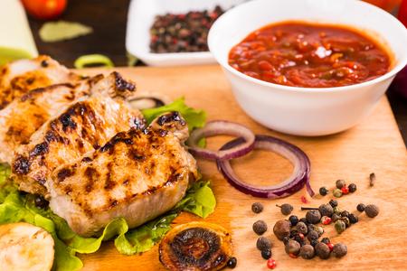 bailar salsa: Primer plano Naturaleza muerta Vista de cerdo a la parrilla o pollo chuletas se reclinan sobre la tabla para cortar madera con un tazón de salsa, verduras y granos de pimienta en rodajas