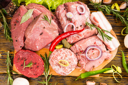 overfilled: Cutting board overfilled with large pieces of meat covered with herbs and peppers ready for cooking Stock Photo