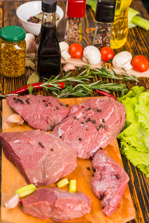 carne roja: Cinco piezas de carne roja cubiertos con ingredientes de granos de pimienta en la tabla de cortar listo para ser cocinado junto a otras verduras, especias y aromas
