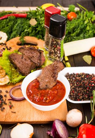 bounty: Cerca de ángulo alto encima de vista de pequeños trozos de carne de vacuno con plato de inmersión de la salsa rodeado de granos de pimienta fresca, hierbas y verduras coloridas del Bounty Foto de archivo